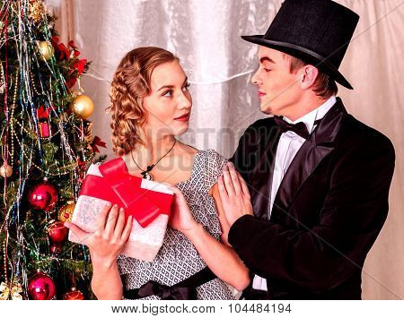 Couple on party near Christmas tree. Black and white retro. Man wearing in cylinder hat.