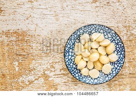 macadamia nuts on a ceramic bowl against rustic barn wood, top view