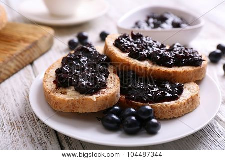 Fresh toast with butter and jam on table close up