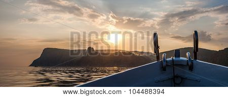 Prow Of The Boat Approaching The Shore At Sunset