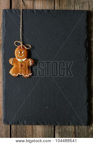 Christmas homemade gingerbread girl over slate background