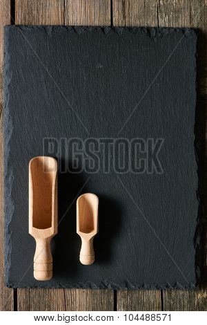 Wooden scoop on slate background