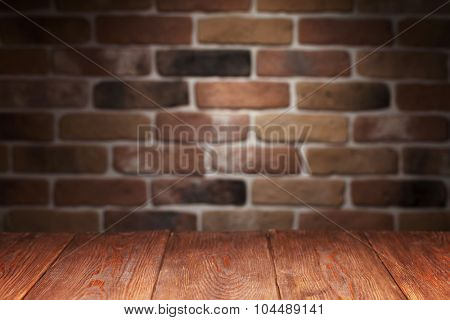 Wooden table and brick wall. View with copy space. Focus on table.