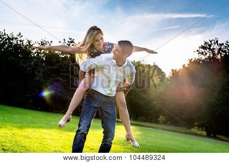 Man carrying girl piggyback in summer in backlit sunset scene