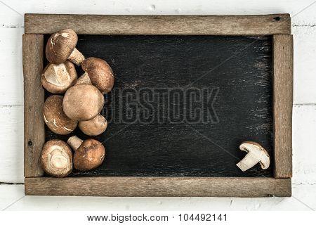 Shiitake Mushrooms On Rustic Wooden Blackboard, Overhead View Of Mushroom On Blackboard