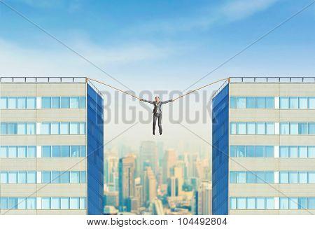 Businesswoman hanging between two skyscrapers