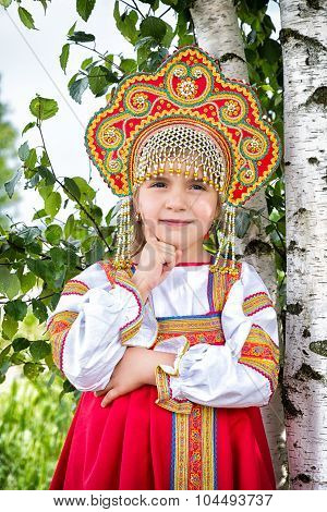 Little Girl In Russian National A Sundress And A Kokoshnik Stand Near A Birch In Summer Day