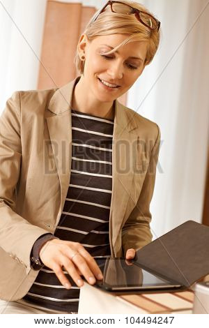 Businesswoman using tablet computer, smiling.