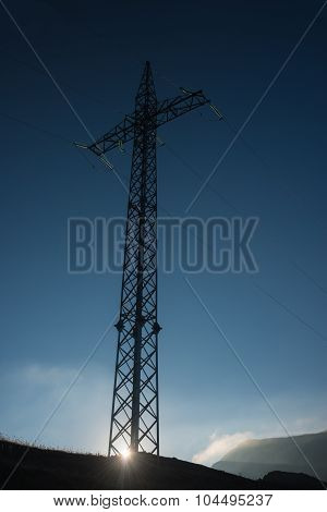 High-voltage Power Line Pylon At Sunrise