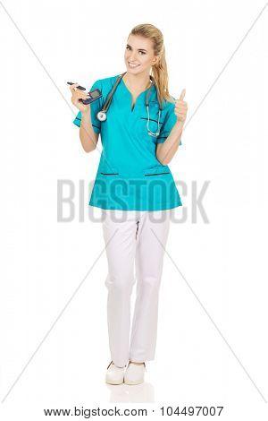 Female nurse or doctor holding glucometer.