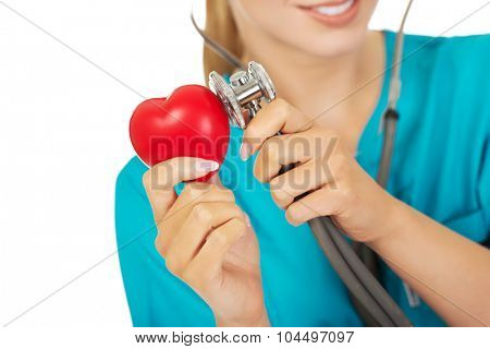 Female doctor listens to the heart through a stethoscope.