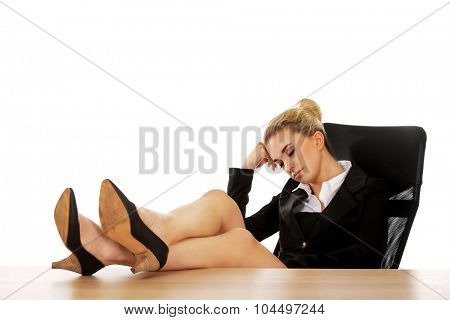 Tired young businesswoman holding legs on the desk.