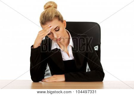 Beautiful worried businesswoman behind the desk.