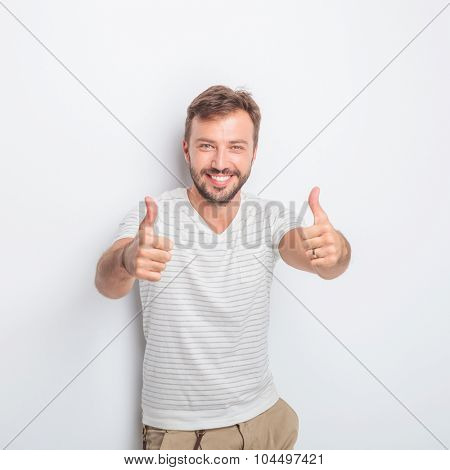 happy young man making the ok thumbs up hand sign with both hands while standing in studio