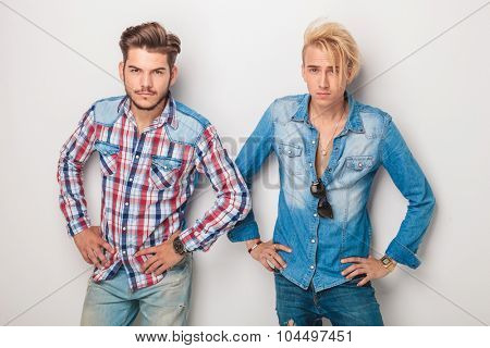 couple of casual dudes standing with hands on hips against studio wall