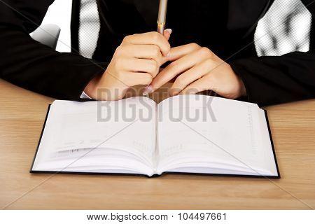 Businesswoman writes note in notebook.