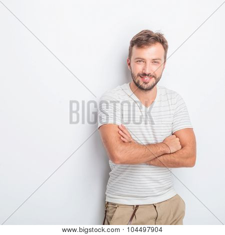 happy young casual man with hands crossed standing in studio