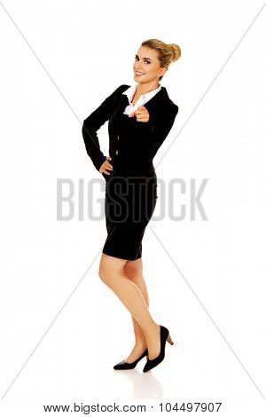 Young smiled businesswoman pointing her finger.