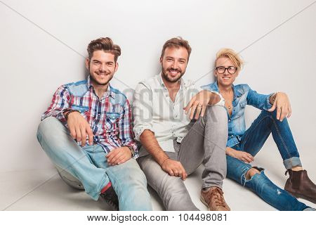 happy group of men laughing for the camera while sitting down on the floor in studio