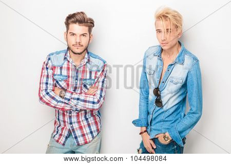 two cool casual men looking at the camera, one with han in pocket and one with arms crossed