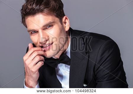 Close up picture of a handsome young business man holding his hand near the mouth.