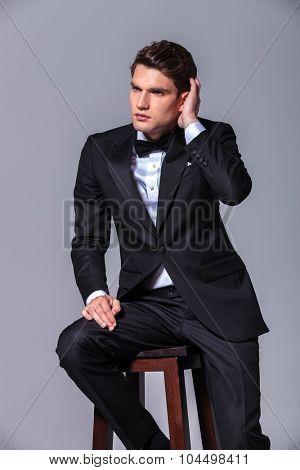 Attractive young business man sitting on a stool while fixing his hair.