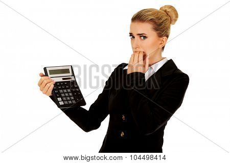 Nervous businesswoman looking at calculator.