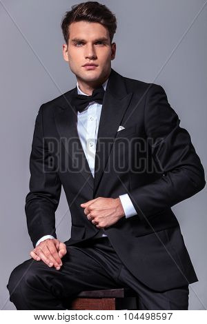 Portrait of a young business man pulling his jacket while sitting on a stool.