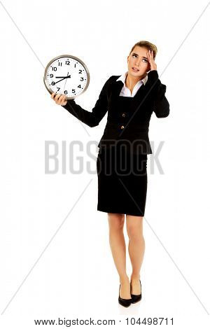 Young businesswoman terrified looks at the clock. Time concept