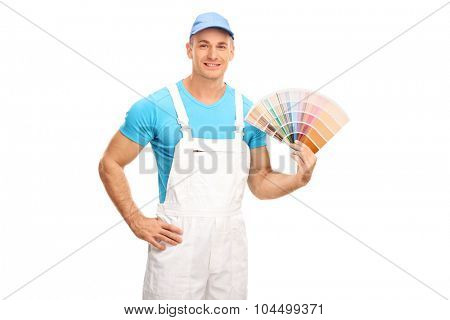 Young male decorator in white jumpsuit holding a color swatch and looking at the camera isolated on white background