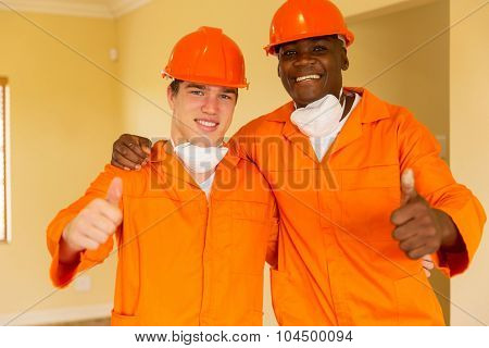 cheerful workmen giving thumbs up inside house