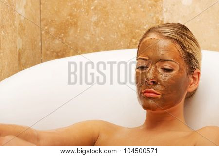 Relaxed spa woman sitting in a bath with closed eyes