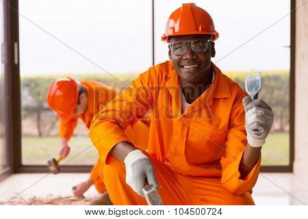 african workman holding chisel and hammer inside house under construction