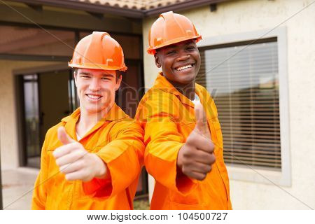 cheerful young construction workers thumbs up outside the house