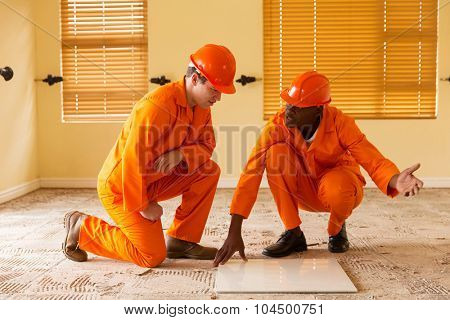 professional construction co-workers discussing floor tiles