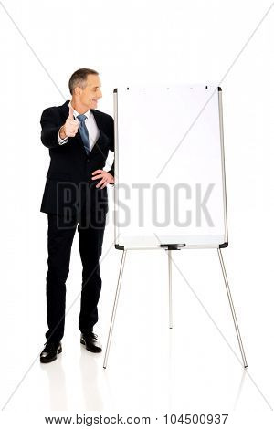 Mature businessman with ok sign near flip chart
