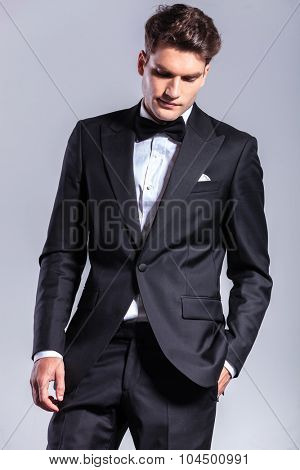 Attractive business man holding his hand in pocket while looking down.