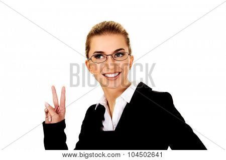 Happy businesswoman shows victory sign.