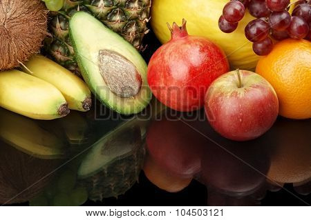 Cropped Shot Of Fruits-grapes,pomegranate,avocado On Black With Reflection