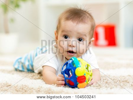 Joyful baby lying on the floor in nursery room