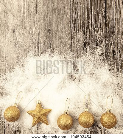 Christmas card with gold Christmas balls, snowballs, winter snow and star on wooden background.