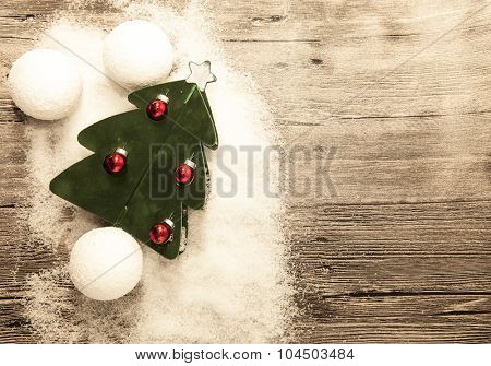 Christmas card with red Christmas balls, snowballs, winter snow and small fir tree on wooden background.