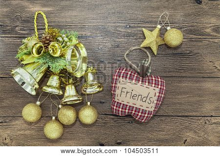 Glittering gold Christmas balls, bells, and star on wooden background. Vintage textile fir tree toy with word Friends