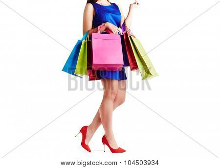 Shopaholic in blue dress holding several multi-color paperbags