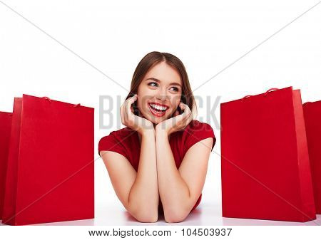 Modern shopper lying between red paperbags