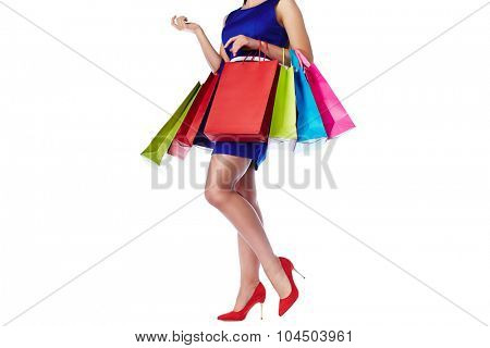 Legs of pretty woman in blue dress with paperbags