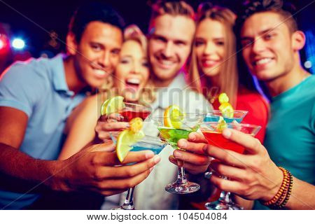 Group of young friends toasting with cocktails