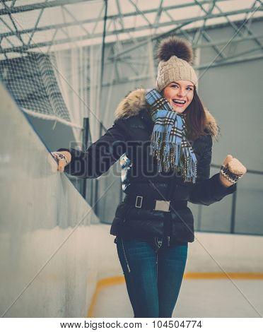 Happy newbie girl on ice skating rink