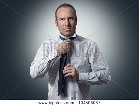 Smiling Businessman Tying A Neck Tie