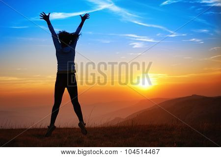 Silhouette Of Happy Jumping Young Woman